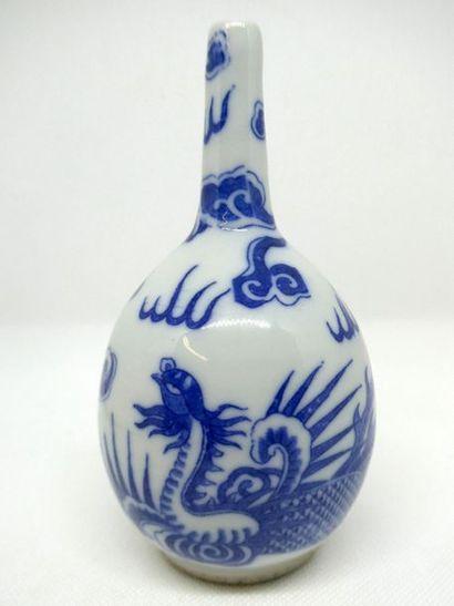 CHINE    Aspersoir en porcelaine blanc et bleu à motifs de dragons.     H. : 16,60...