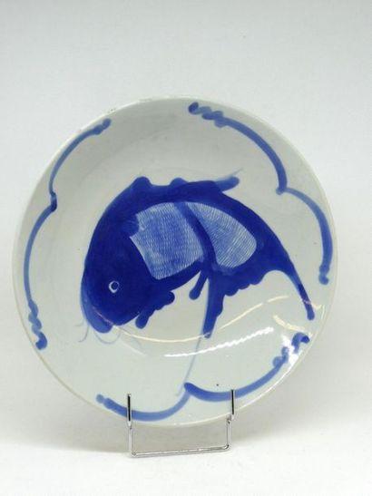 Plat en porcelaine à décor en blanc et bleu de poissons.    Diam. : 23, 6 cm