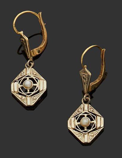 PAIRE DE BOUCLES D'OREILLE en or jaune 18K (750) serties en leur centre d'une perle....