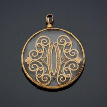 PENDENTIF en or jaune 750 mm formé d'un motif en or ciselé et ajouré, cerclé dans...