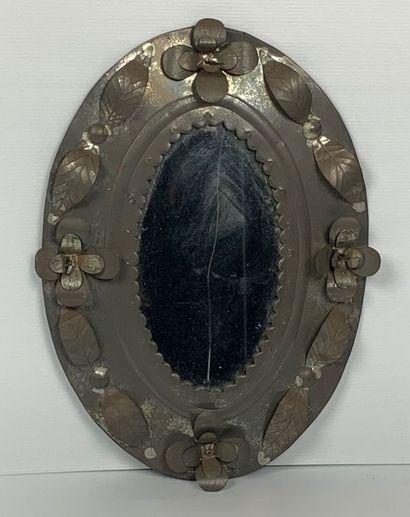 Miroir ovale en tôle bordé à décor appliqué...