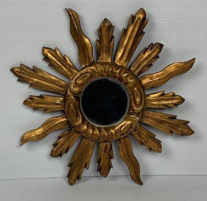 Miroir en bois doré figurant un soleil rayonnant....