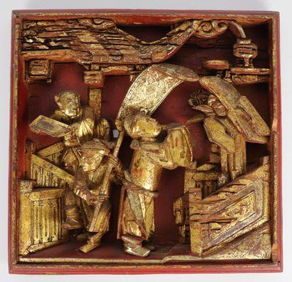 CHINE.  Panneau en bois sculpté, laqué rouge et doré figurant trois personnages....