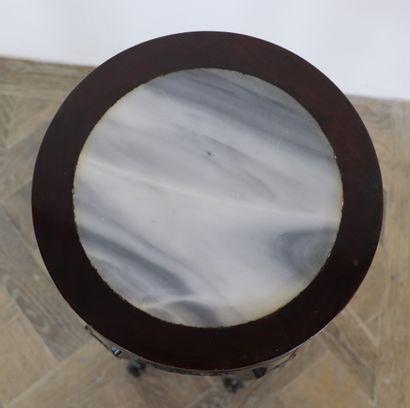 CHINE.  Sellette en bois exotique sculpté, le plateau en marbre veiné.  Elle repose...