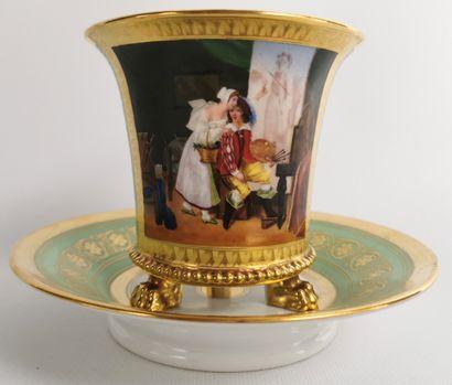 PARIS.  Importante tasse et sa sous-tasse en porcelaine, à fond vert et or, à décor...