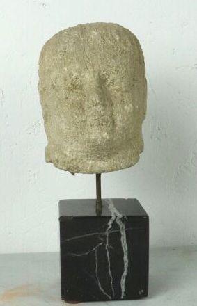 Tête d'homme en pierre sculptée.  Sur un...