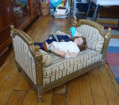 Lit de poupée en bois doré à décor de godrons...
