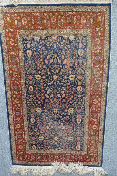 Petit tapis persan à décor de rinceaux sur...