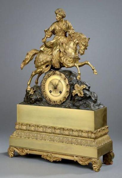 PENDULE en bronze doré et patiné à décor...