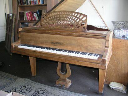 Piano quart de queue en bois naturel posant...