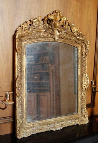Miroir en bois doré à décor de coquille ajourée...
