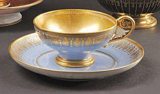 SÈVRES Tasse à thé et sa soucoupe à décor de palmettes or sur fond bleu agate, intérieur...