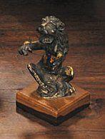 Lion assis en bronze ciselé et doré représenté sur ses pattes postérieures tenant...
