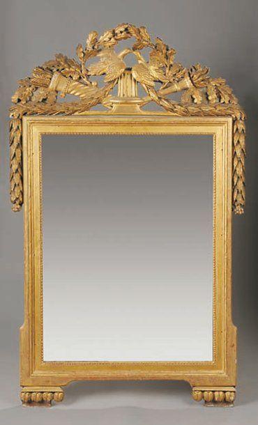 Glace en bois sculpté et doré à décor de...