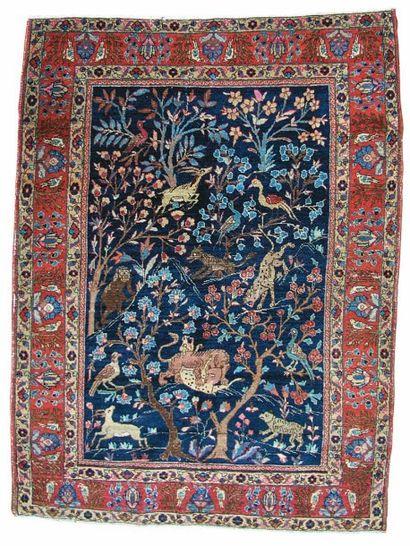Tapis persan à décor d'animaux dans des branchages sur fond bleu. Bordure à décor...