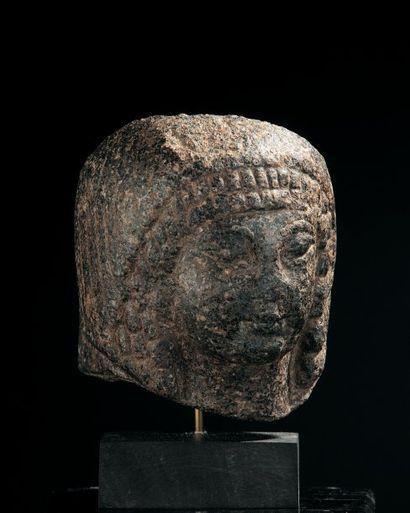 TÊTE féminine provenant d'une statuette. Les yeux et la chevelure en petites mèches...
