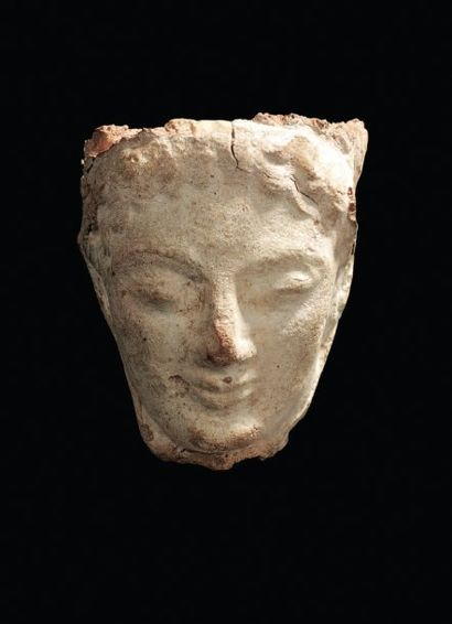 TÊTE provenant probablement d'une statuette votive archaïque. Terre cuite beige....