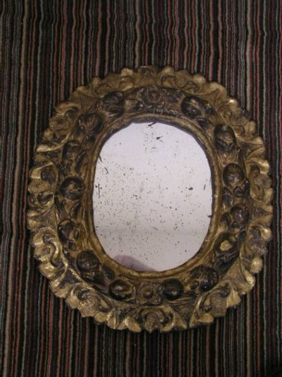 Miroir ovale en bois mouluré et doré, sculpté de guirlande de fruits et feuillage....