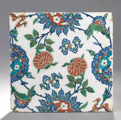 IZNIK. CARREAU en céramique siliceuse à glaçure plombifère à décor polychrome d'oeillets...