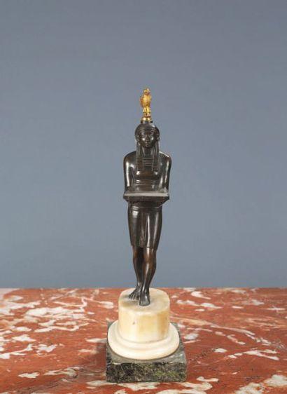 Egyptien portant un plateau en bronze ciselé,...