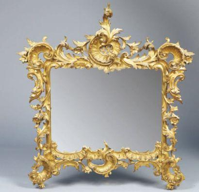 Glace en bois doré à riche décor sculpté...