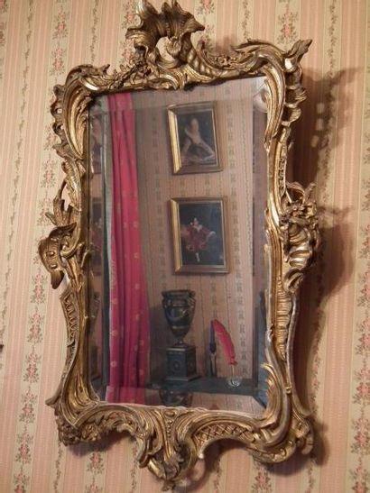 Petit miroir en bois doré à décor sculpté...