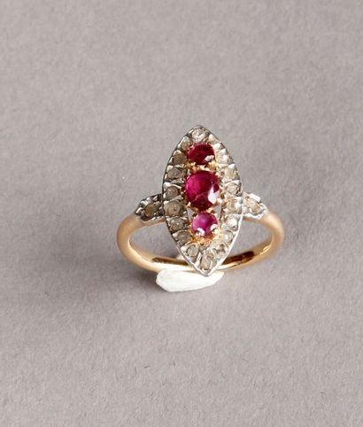 BAGUE marquise ornée de trois rubis (dépolis) dans un entourage de diamants taillés...