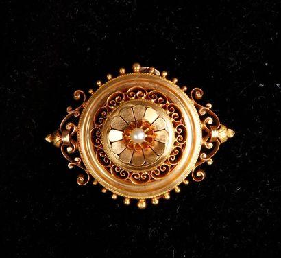 BROCHE circulaire en or jaune ajouré à décor de rinceaux et volutes, ornée d'une...