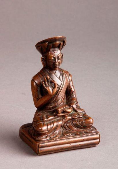 Petit GOUROU tibétain en bronze représenté assis portant un livre (revers découpé...