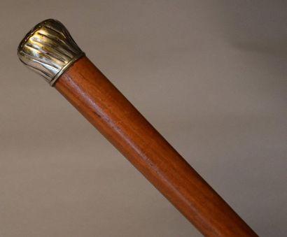 Canne en bois verni. Pommeau en métal argenté...