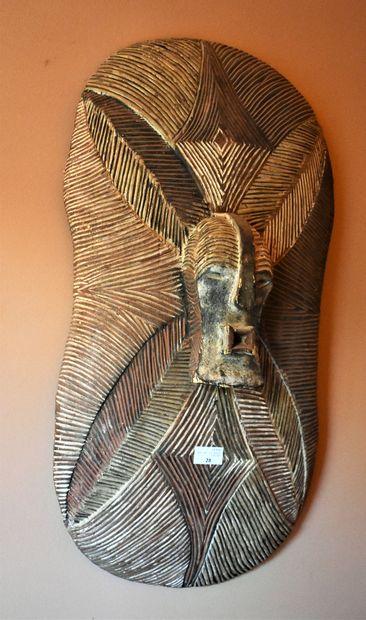BOUCLIER à décor de masque en bois peint....