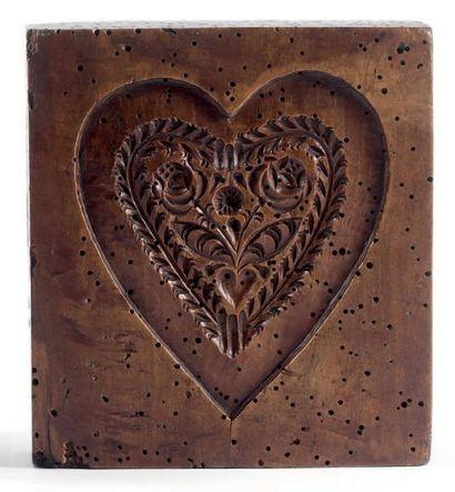 Moule à pain d'épices en noyer sculpté d'un coeur garni de trois fleurs. Passages...