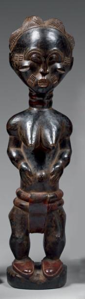 Statuette féminine du type colon. Bois noirci...