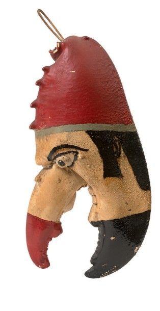 Tête grotesque au bonnet rouge. Grosse pince...