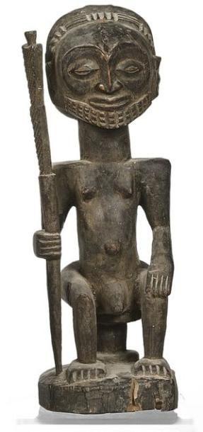 Statuette masculine assise portant une lance....
