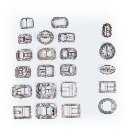 Dix-sept boucles en argent à ardillon (573 g.) et cinq boucles en métal.
