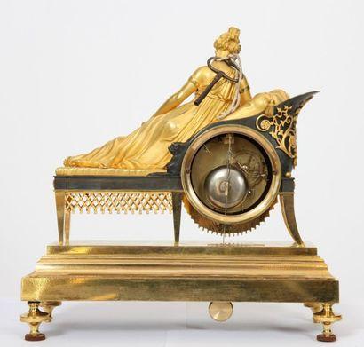 """PENDULE DITE """" RECAMIER"""" Représentant une jeune femme lisant, allongée sur une chaise..."""