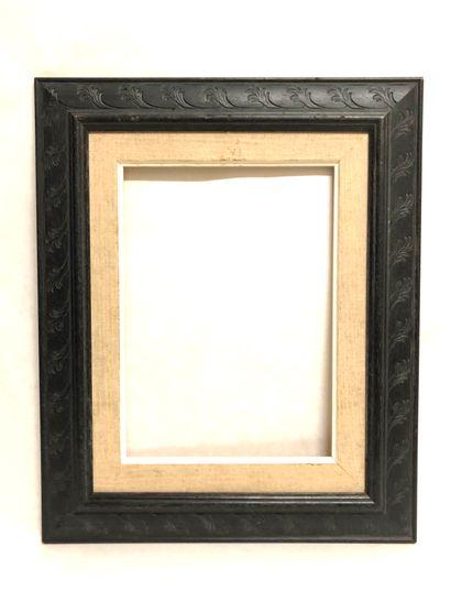 CADRE en bois peint noir à décor incisé de...