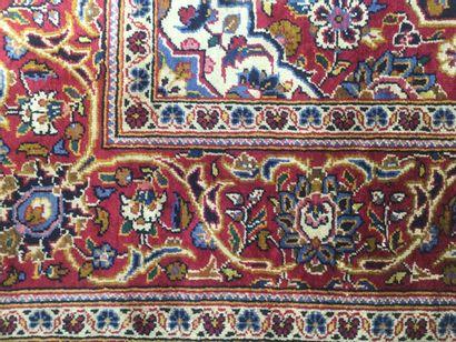 TAPIS KASHAN soie à décor de médaillon central, fleurs et rinceaux sur fond rouge,...