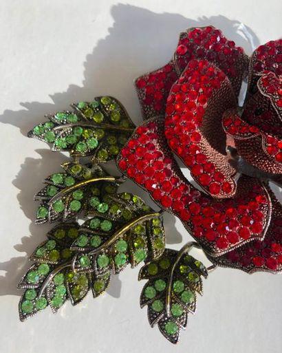 Grande broche en métal à décor d'une grand rose feuillagée sertie de pierres rouges...