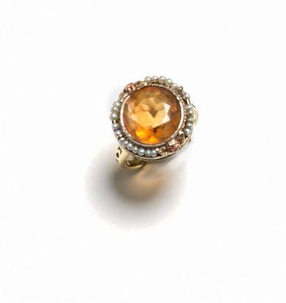 Bague en or jaune 18K (750°/°°) sertie d'une citrine ronde dans un entourage de...