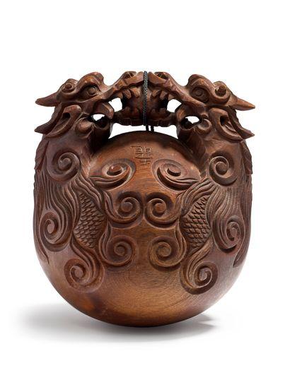 JAPON - XXe siècle Mokugyo en bois, la poignée sculpté de deux poissons-dragons affrontés...