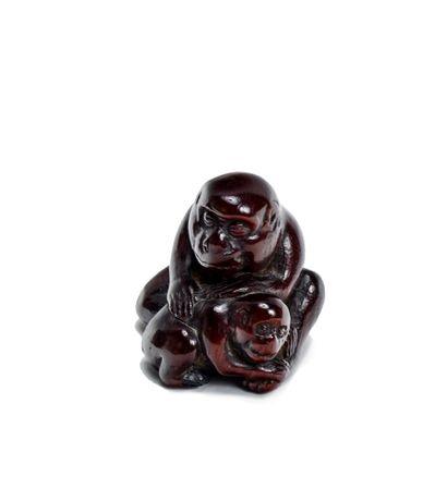 JAPON - XIXE SIÈCLE Netsuke en bois, singe épouillant son petit blotti contre lui....