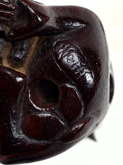 JAPON - XIXE SIÈCLE Netsuke en bois, personnage stylisé assis dans le creux d'un...