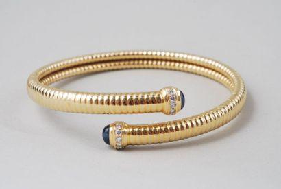 Bracelet « tubogaz » en or jaune 18K serti de deux saphirs taille cabochon, et de...