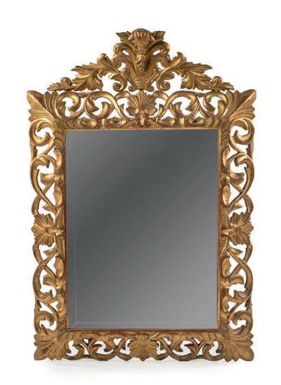 Miroir en bois sculpté et doré à décor ajouré...