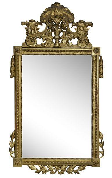 Grand miroir en bois sculpté et doré à décor...