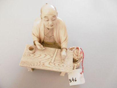 JAPON - Epoque MEIJI (1868 - 1912) Okimono en ivoire, lettré assis à une table, une...