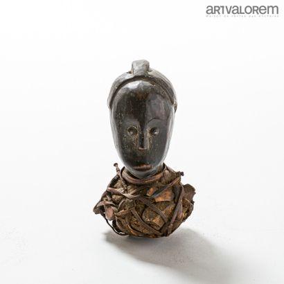 Petite tête FANG (Gabon). Tête enfouie dans un reliquaire fait de cuir et de fibres....