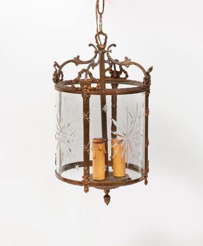 Lanterne cylindrique vitrée en métal doré, à trois lumières et décor gravé étoilé....